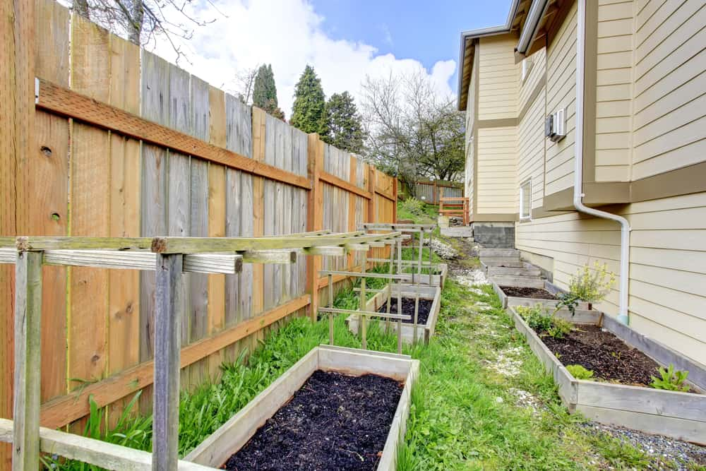 Small,Fenced,Side,Yard,With,Garden,Bed,,Trellis,And,Grid.