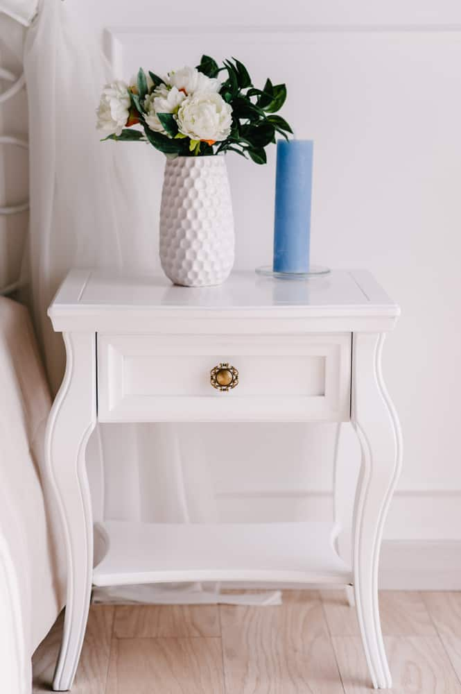 White,Wood,Bedside,Table,,Dresser,In,Bedroom.,Bouquet,On,The